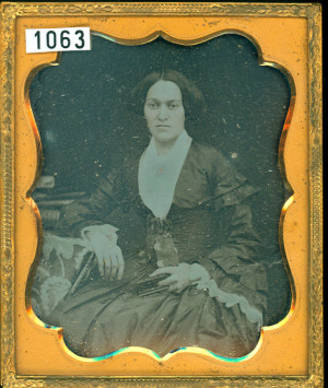 Lady holding a Union Case as she poses for her daguerreotype